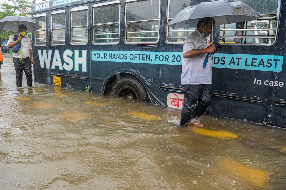 Commuters wade past a stranded bus on a flooded road during a heavy monsoon rain in Mumbai on August 4, 2020. (Photo by INDRANIL MUKHERJEE/AFP via Getty Images)