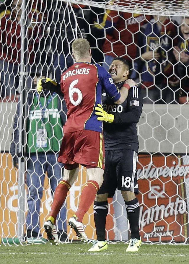 CORRECTS SCORE - Real Salt Lake defender Nat Borchers (6) jumps in to the arms of goalie Nick Rimando (18) at the end of their second leg of the MLS Western Conference semifinal Thursday, Nov. 7, 2013, in Sandy, Utah. Real Salt Lake won 2-0. (AP Photo/Rick Bowmer)