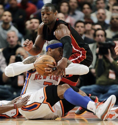 Miami Heat guard Dwyane Wade, above, reaches for the ball with New York Knicks forward Carmelo Anthony trying to retain possession during the first half of Game 3 of an NBA basketball first-round playoff series at Madison Square Garden in New York, Thursday, May 3, 2012. (AP Photo/Kathy Willens)