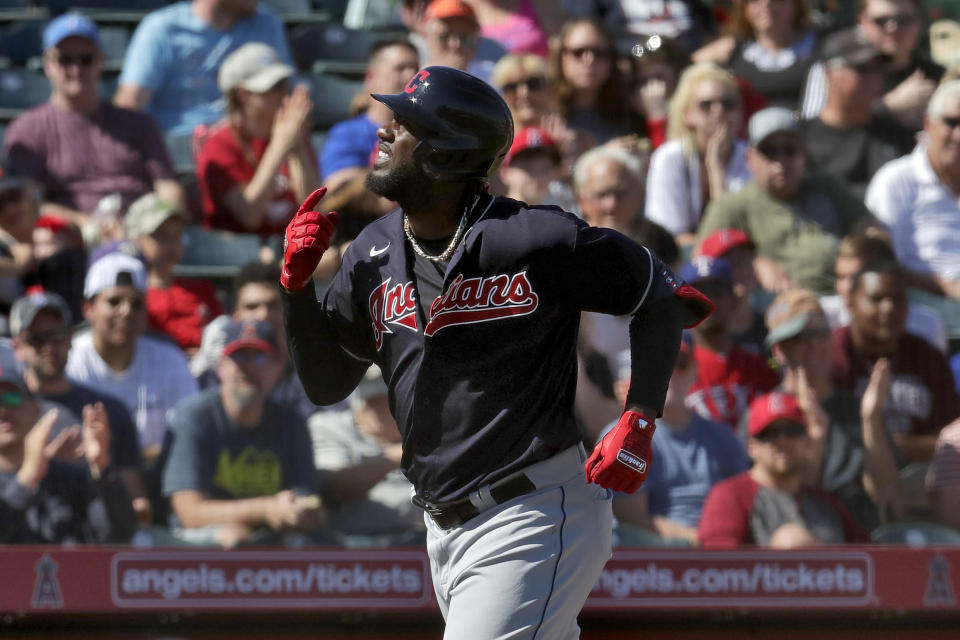 Cleveland Indians' Franmil Reyes celebrates his three run home run as he rounds the bases during the third inning of a spring training baseball game against the Los Angeles Angels Monday, March 9, 2020, in Tempe, Ariz. (AP Photo/Matt York)