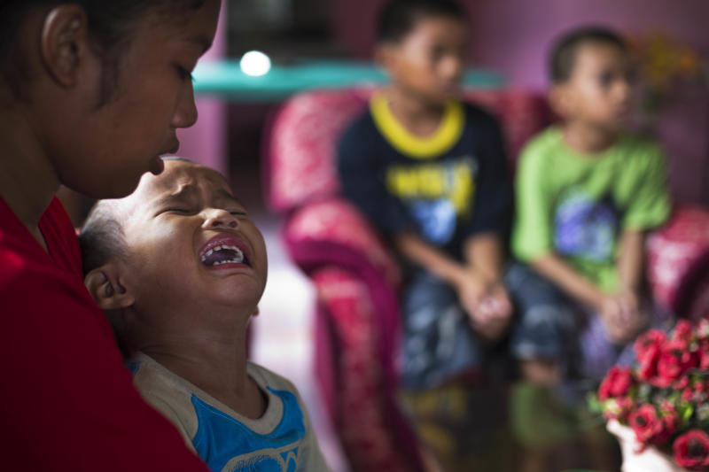 In this Nov. 21, 2013 photo, Shylyny Therese Negru, 15, holds her youngest brother Rainier Aaron Dacuno, 3, as they sit in a relative's home in the town of Burauen, the Philippines. On the right are two other siblings, Richard Chris Negru, 12, and Richard Aaron Dacuno, 6. The children are among an unknown number of children in the eastern Philippines who lost their parents to the massive Nov. 8 storm. (AP Photo/David Guttenfelder)
