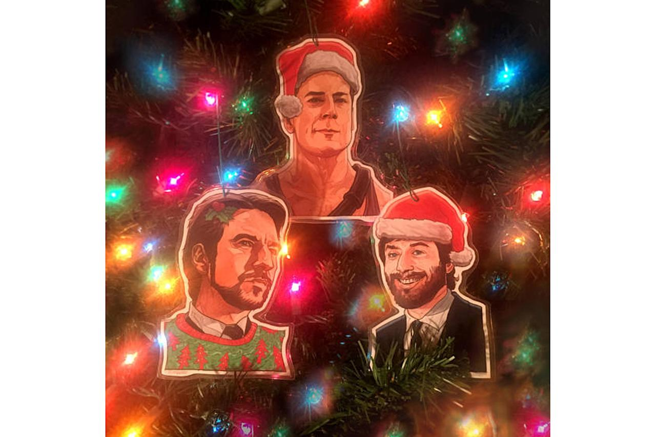 """<p>If you believe <em>Die Hard</em> is the ultimate Christmas movie, this set of three placards featuring John McClane, Hans Gruber, and Ellis will have you caroling """"Yippee ki yay."""" <a rel=""""nofollow"""" href=""""https://www.etsy.com/listing/512083354/die-hard-christmas-ornament-3-pack-combo?ref=bestselling_by_query-1""""><strong>Buy here</strong></a> </p>"""