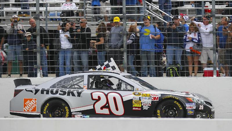 NASCAR driver Matt Kenseth takes a victory lap with the checkered flag after winning the NASCAR Sprint Cup Series auto race at New Hampshire Motor Speedway in Loudon, N.H., Sunday, Sept. 22, 2013, (AP Photo/Cheryl Senter)