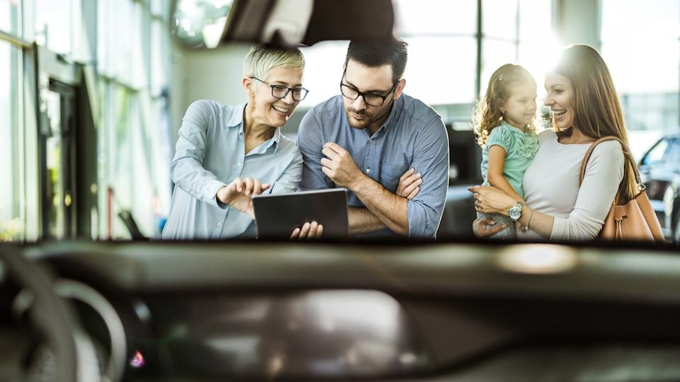 Happy family and car salesperson using touchpad in a showroom.