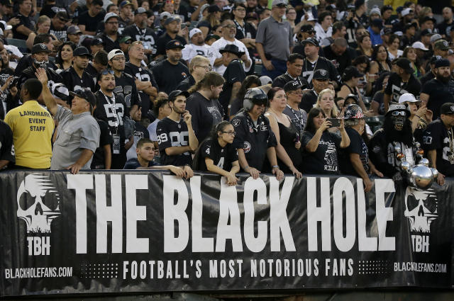 """FILE - In this Aug. 31, 2017, file photo, Oakland Raiders fans watch from the Black Hole section of Oakland Alameda County Coliseum during the first half of an NFL preseason football game between the Raiders and the Seattle Seahawks in Oakland, Calif. The slow, agonizing demise of the Oakland Raiders will continue for at least one more season. There will be one more """"final"""" home game at the Oakland Coliseum, Dec. 15 against the Jacksonville Jaguars. There have been possible """"final"""" home games for a few years now because the Raiders have essentially had one foot out the door since 2015, when they joined with the AFC West rival Chargers in a failed attempt to build a stadium in the Los Angeles suburb of Carson. (AP Photo/Eric Risberg, File)"""
