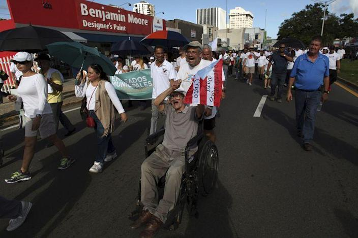 FILE PHOTO: People take part in a march to improve healthcare benefits in San Juan, Puerto Rico