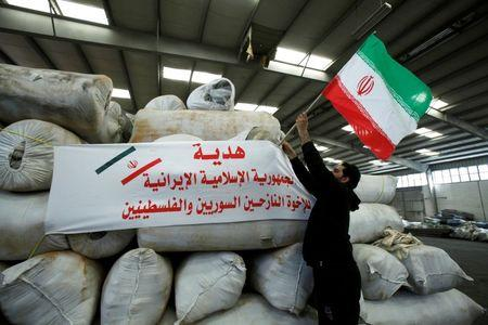 A man places an Iranian flag on bags of Iranian humanitarian aid at the port of Beirut