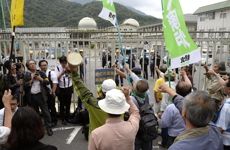 Protesters punch the air in front of a gate of the Takahama nuclear power station, background, after a freighter carrying MOX, a mixture of uranium and plutonium oxide, arrived in Takahama town, Fukui prefecture, Japan, Thursday, June 27, 2013. The power plant on the Sea of Japan coast has received the first shipment of reprocessed nuclear reactor fuel sent from France since the 2011 disaster that forced it to shut down reactors. Operators of the plant are hoping to use the fuel once they get the go-ahead to restart their reactors. (AP Photo/Kyodo News) JAPAN OUT, MANDATORY CREDIT