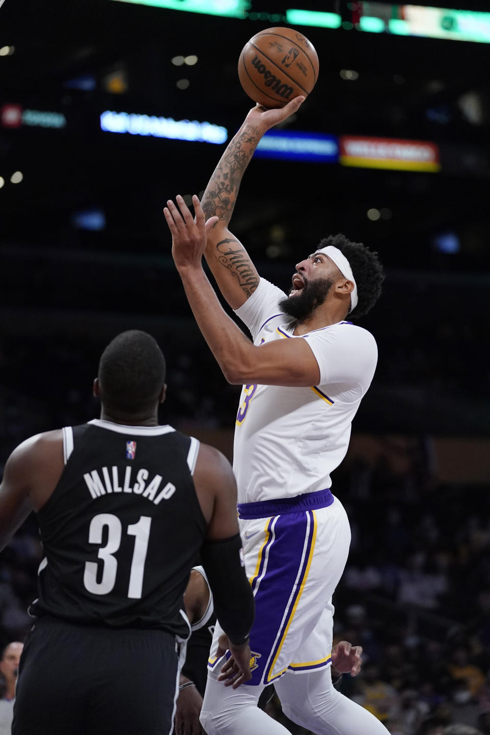 Los Angeles Lakers forward Anthony Davis, right, shoots as Brooklyn Nets forward Paul Millsap defends during the first half of a preseason NBA basketball game Sunday, Oct. 3, 2021, in Los Angeles. (AP Photo/Mark J. Terrill)