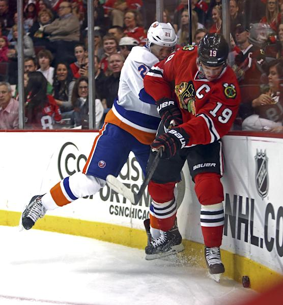 New York Islanders' Kyle Okposo checks Chicago Blackhawks' Jonathan Toews during the first period of an NHL hockey game in Chicago on Friday, Oct. 11, 2013. (AP Photo/Charles Cherney)