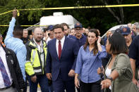 Florida Gov. Ron DeSantis, center left, and Lt. Gov. Jeanette Nunez, center right, arrive for a news conference near the scene where a wing of a 12-story beachfront condo building collapsed, Thursday, June 24, 2021, in the Surfside area of Miami. (AP Photo/Lynne Sladky)