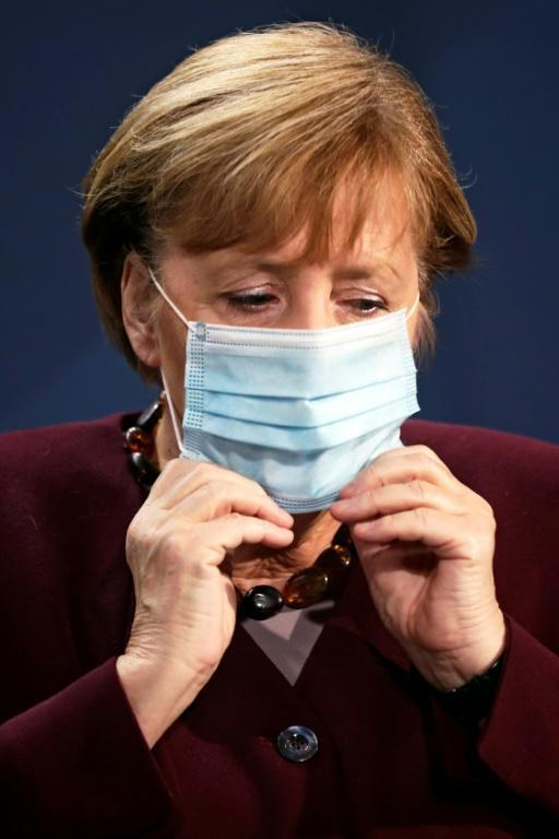 German Chancellor Angela Merkel puts on her face mask after addressing a press conference after taking part in the G20 summit by video