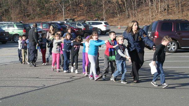 Two Connecticut State Police officers escort a class of students and two adults out of Sandy Hook Elementary School in Newtown, Conn., Dec. 14, 2012, after a shooter entered the building and killed 20 children and six adults before taking his own life. (Shannon Hicks/Newtown Bee via Polaris)