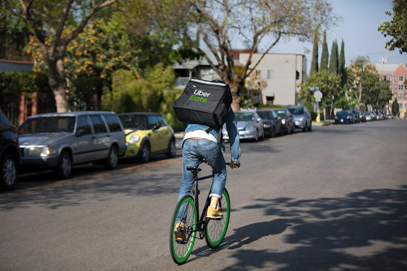 An Uber Eats courier makes a delivery by bike.