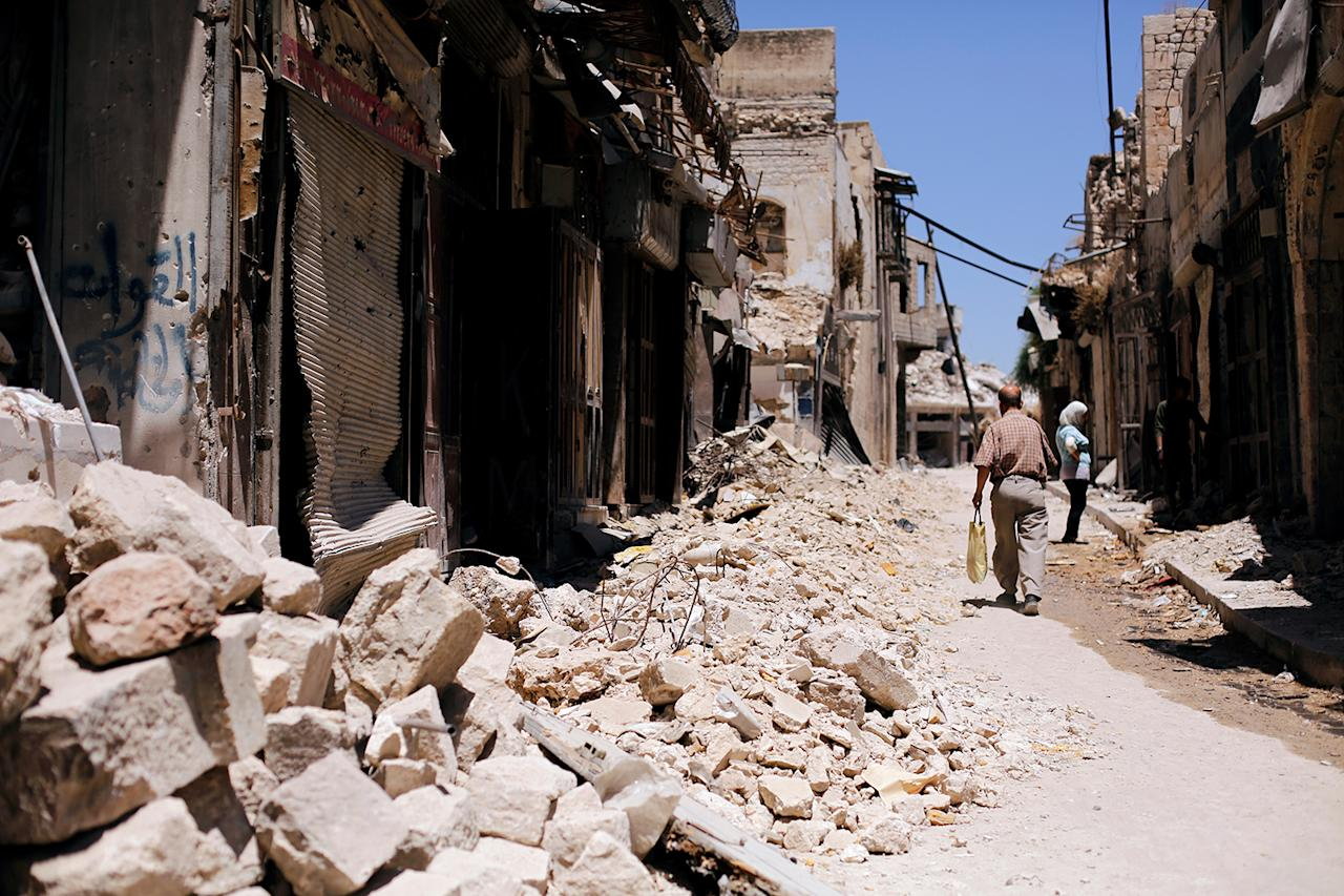 <p>A man walks past damaged houses in the Old City of Aleppo, Syria, July 13, 2017. (Photo: Omar Sanadiki/Reuters) </p>