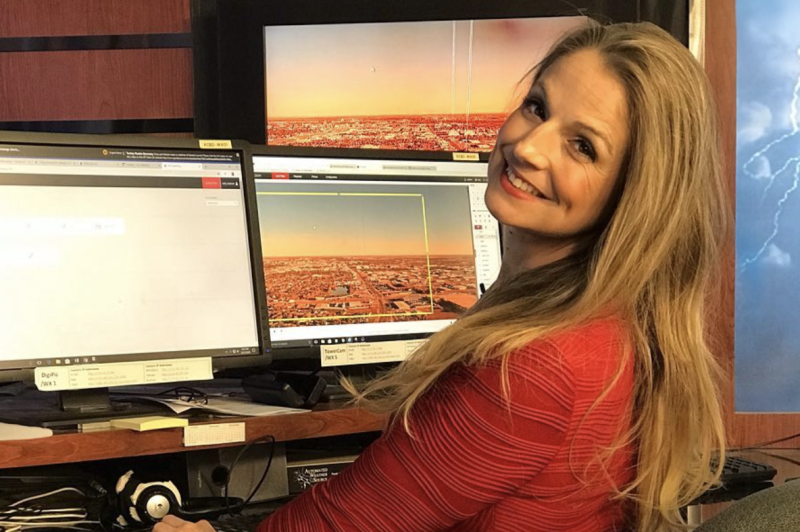 Kelly Plasker sits in front of computer screens at a TV studio.