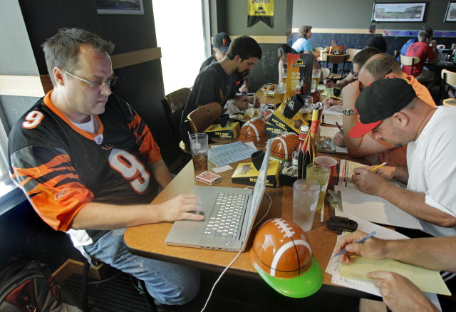 FILE - This Aug. 30, 2010, file photo shows Brian Sherman, left, using his laptop to record moves in his team's fantasy football draft, at a Buffalo Wild Wings restaurant in Cincinnati. From 2007 to 2017, the number of people playing fantasy football more than tripled, from 13.8 million to 42.7 million, according to the Fantasy Sports & Gaming Association. This past Sunday, ESPNs fantasy app drew 8.3 million unique users _ its biggest day ever _ according to ESPN and Adobe Analytics (AP Photo/Al Behrman, File)