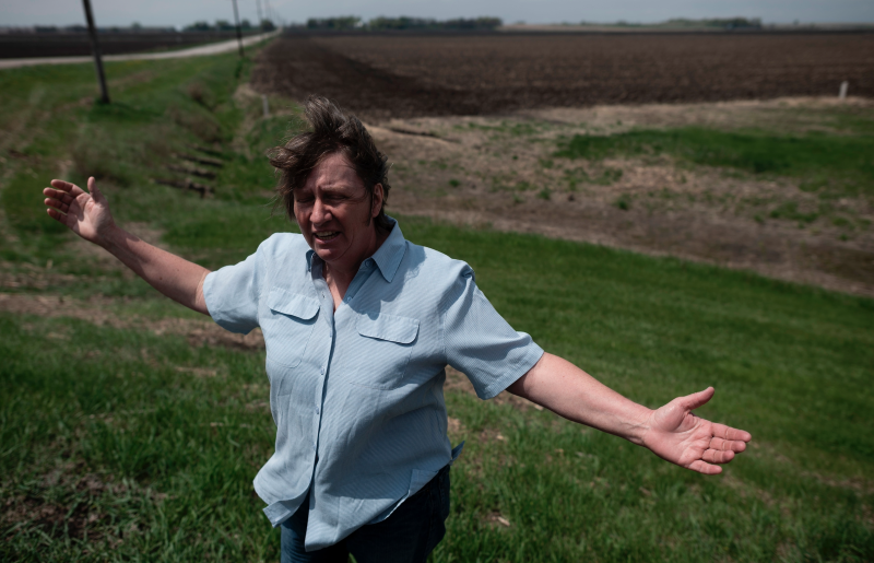 Ruth, wife of farmer Sid Ready, gestures as she stands on the ditch which hold most of the flood water away from their farm near Scribner, Nebraska on May 5, 2019. (Photo: Johannes EISELE / AFP)
