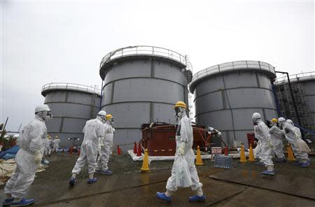 File photo of members of the media and TEPCO employees wearing protective suits and masks walking past storage tanks in Fukushima prefecture