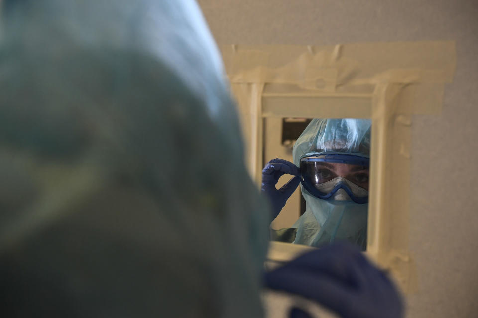 A member of the medical team prepares to treat coronavirus patients in the ICU department of the Clinica Universitaria, in Pamplona, northern Spain, Tuesday, Feb. 2, 2021. Spain's virus expert for the coronavirus pandemic says infections in the country are losing steam but that the contagion curve needs to be bent much further to safeguard the health system. (AP Photo/Alvaro Barrientos)