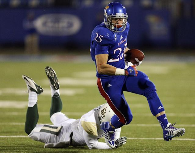 Kansas Jayhawks running back Brandon Bourbon (25) slips past Baylor Bears cornerback Ryan Reid for a touchdown in the third quarter of an NCAA college football game Saturday, Oct. 26, 2013, in Lawrence, Kan. Baylor won 59-14. (AP Photo/Ed Zurga)