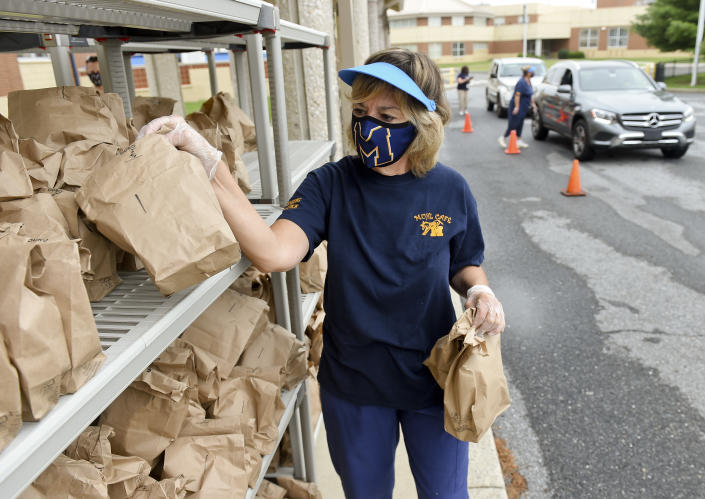 Joan Sandritter, a cafeteria worker, gets grab-and-go breakfasts and lunches from a rack, to distribute them to families who drive up at Muhlenberg Elementary Center in Muhlenberg Twp., PA. (Photo by Ben Hasty/MediaNews Group/Reading Eagle via Getty Images)