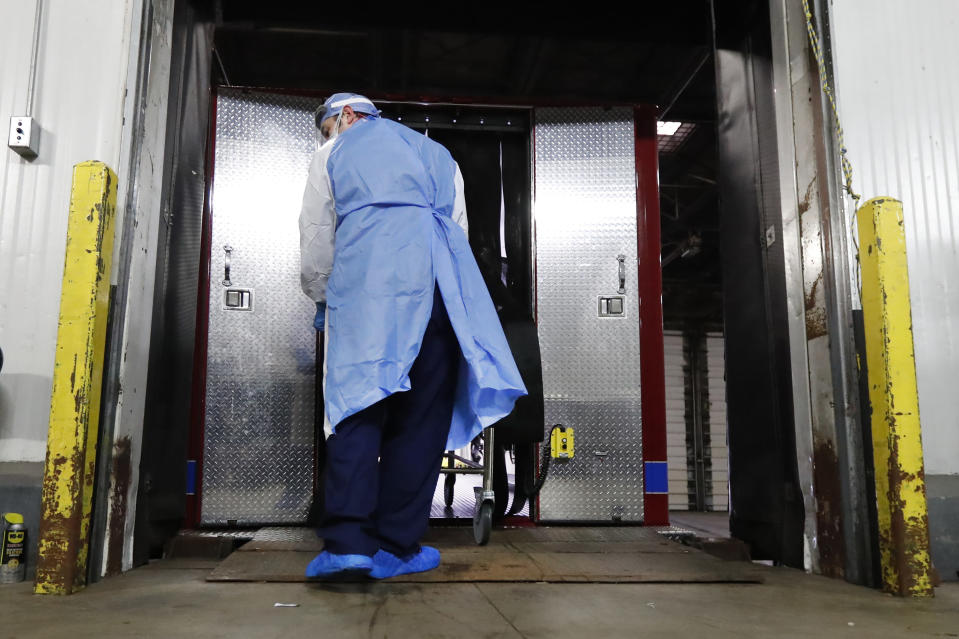 In this Tuesday, May 5, 2020, photo, Cook County Medical Examiner forensic technician Pero Paunovich wheels the body of a COVID-19 victim from an emergency-management truck that just arrived at the medical examiner's auxiliary surge storage center in Chicago. An encouraging sign amid the grimness is that two of the rooms are mostly empty, an indication the medical examiner's system to ensure most bodies are released to funeral homes as quickly as possible is working. (AP Photo/Charles Rex Arbogast)