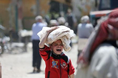 A boy gestures as he holds stacks of bread in the city of Douma, Damascus, Syria April 16, 2018. REUTERS/Ali Hashisho