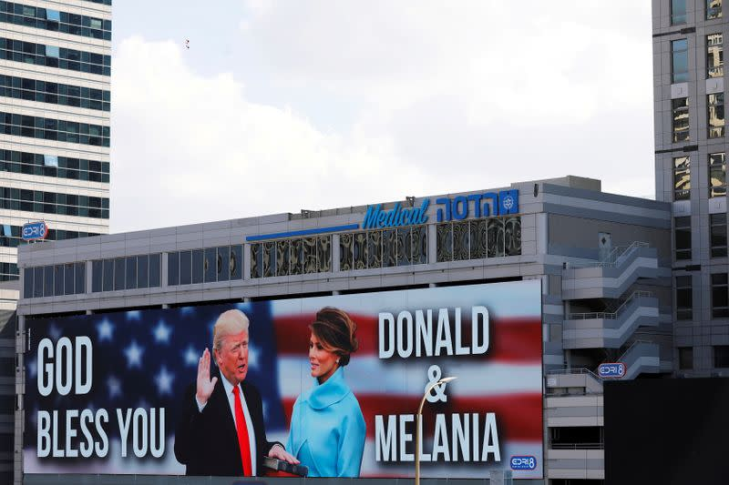 """FILE PHOTO: A billboard depicting U.S. President Donald Trump and his wife Melania with the American flag and the words, """"God Bless You"""" is seen along a highway in Tel Aviv, Israel"""