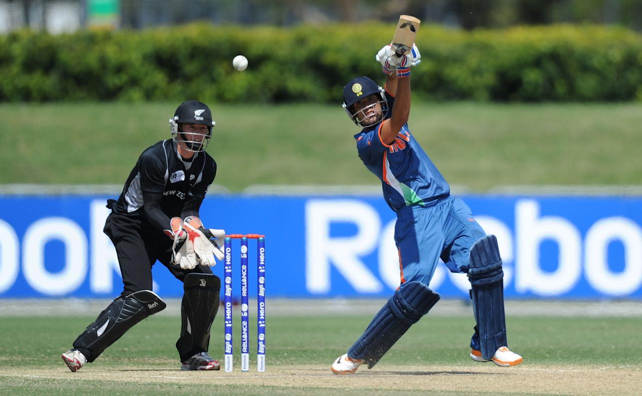TOWNSVILLE, AUSTRALIA - AUGUST 23:  Prashant Chopra of India drives down the ground as Cameron Fletcher of New Zealand stands over the stumps during the ICC U19 Cricket World Cup 2012 Semi Final match between India and New Zealand at Tony Ireland Stadium on August 23, 2012 in Townsville, Australia.  (Photo by Malcolm Fairclough-ICC/Getty Images)