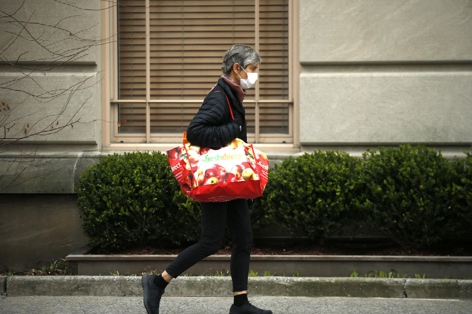 NEW YORK, NY - MARCH 30: A woman carries a bag on Fifth Avenue as New York City attempts to slow down the spread of coronavirus through social distancing on March 30, 2020. New York has been hit hard by the restrictions in response to the outbreak of COVID-19. (Photo by John Lamparski/Getty Images)