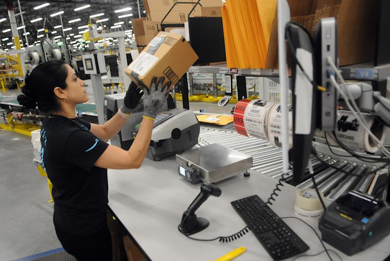 An Amazon associate processes a package for delivery at an Amazon Robotics fulfillment center during its first public tour on April 12, 2019 in the Lake Nona community of Orlando, Florida. The over 855,000 square foot facility opened on August 26, 2018 and employs more than 1500 full-time associates who pick, pack, and ship customer orders with the assistance of hundreds of robots which can lift as much as 750 pounds and drive 5 feet per second. (Photo by Paul Hennessy/NurPhoto via Getty Images)