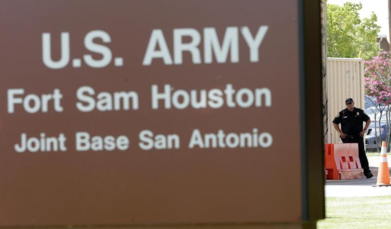A guard stands at a gate to Fort Sam Houston, Monday, June 10, 2013, in San Antonio.  San Antonio police have arrested a gunman for shooting at the main gate of the U.S. Army post.  (AP Photo/Eric Gay)