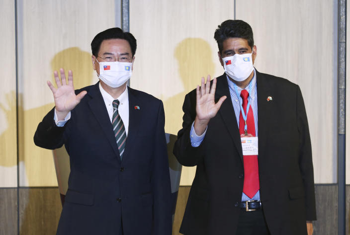 Palau President Surangel Whipps, right, and Taiwanese Foreign Minister Joseph Wu wave for the media at a news conference in Taipei, Taiwan, Monday, March 29, 2021. Whipps arrived in Taiwan on Sunday, a five-day visit to kick-off a Taiwan-Palau travel bubble that starts April 1. (AP Photo/Chiang Ying-ying)