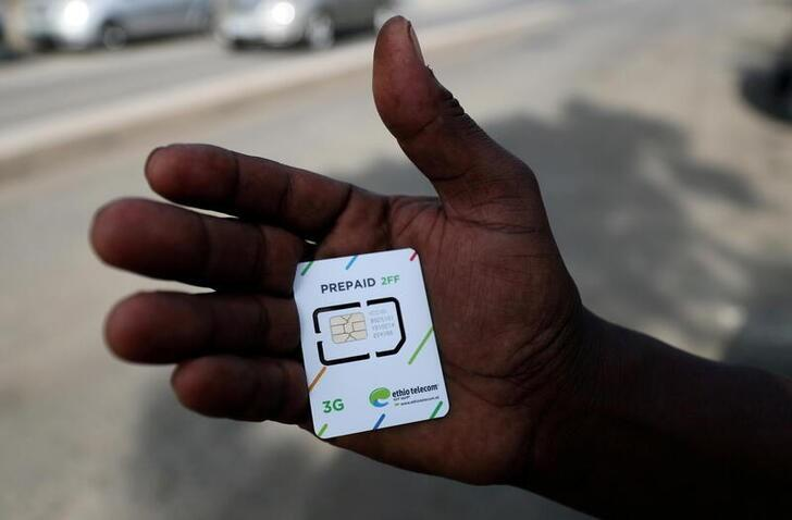 FILE PHOTO: A customer holds a 3G prepaid sim card after buying the service from an Ethio-Telecom shop in Addis Ababa