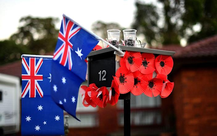 A mailbox is decorated with Australia's national flags and poppies flowers during the Anzac Day - Saeed Khan/AFP