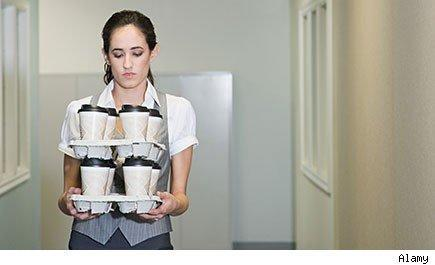 young woman carrying two trays of stacked coffee cups