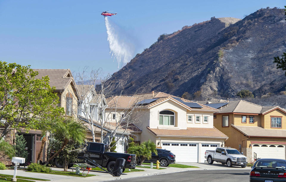 A helicopter drops water onto hot spots of the Silverado Fire behind homes in the Foothill Ranch area near Lake Forest, Calif., Wednesday, Oct. 28, 2020. (Mark Rightmire/The Orange County Register via AP)