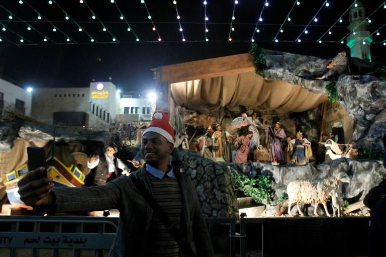 A man takes a selfie at the Manger Square outside the Church of the Nativity during Christmas Eve celebrations Bethlehem