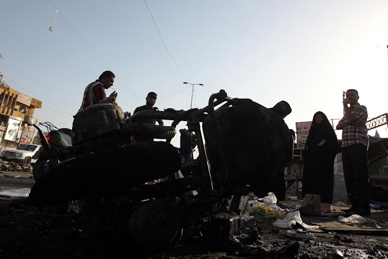 Iraqi onlookers gather on July 16, 2014 at the scene of an explosion in Sadr City, one of Baghdad's northern Shiite-majority districts