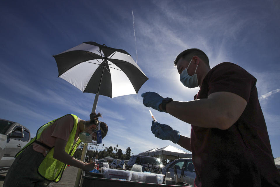 Dr. Richard Dang, right, Assistant professor USC School of Pharmacy prepares a COVID-19 vaccine as mass-vaccination of healthcare workers starts at Dodger Stadium on Friday, Jan. 15, 2021, in Los Angeles. (Irfan Khan/Los Angeles Times via AP, Pool)