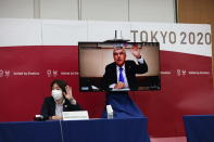 International Olympic Committee (IOC) president Thomas Bach (on-screen) and Tokyo 2020 president Seiko Hashimoto, left, wave at the beginning of the five-party meeting in Tokyo, Thursday, July 8, 2021. (Behrouz Mehri/Pool Photo via AP)