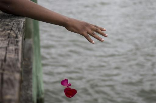 Guests take part in a flower petal throwing ceremony to honor Africans who passed away at sea during the Atlantic slave trade during the 2019 African Landing Commemorative Ceremony on August 24, 2019 in Hampton, Virginia