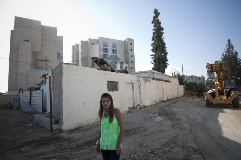"In this photo taken on Thursday, Sept. 20, 2012, Israeli Arab activist Horia Elsadi poses for a photograph in front of new housing project for religious Jews in Israel's mixed Arab-Jewish town of Lod, central Israel. Religious Jews who are the bedrock of the settlement movement have marked Israel's mixed Arab-Jewish cities as the new front to ""reclaim,"" pushing into Arab neighborhoods to cement the Jewish presence there. The migration of several thousand devout Jews to rundown areas of Jaffa, Lod, Ramle and Acco has had a divisive effect far outweighing their absolute numbers, with Jews celebrating _ and Arab activists eyeing with mistrust and resentment _ the construction of Jewish seminaries and housing developments marketed exclusively to Jews. (AP Photo/Ariel Schalit)"