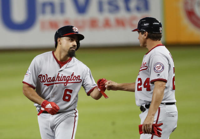 Washington Nationals' Anthony Rendon (6) is congratulated by first base coach Tim Bogar (24) after Rendon got a base hit during the first inning of a baseball game against the Miami Marlins, Tuesday, Sept. 18, 2018, in Miami. (AP Photo/Wilfredo Lee)
