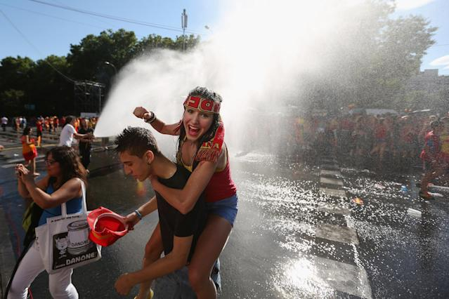 MADRID, SPAIN - JULY 02: Supporters of Spain's national football team are hosed down by a fireman before congratulating their team's players on their return to Madrid following their victory in UEFA EURO 2012 football championships on July 2, 2012 in Madrid, Spain. Spain beat Italy 4-0 in the UEFA EURO 2012 final match in Kiev, Ukraine, on July 1, 2012. (Photo by Oli Scarff/Getty Images)