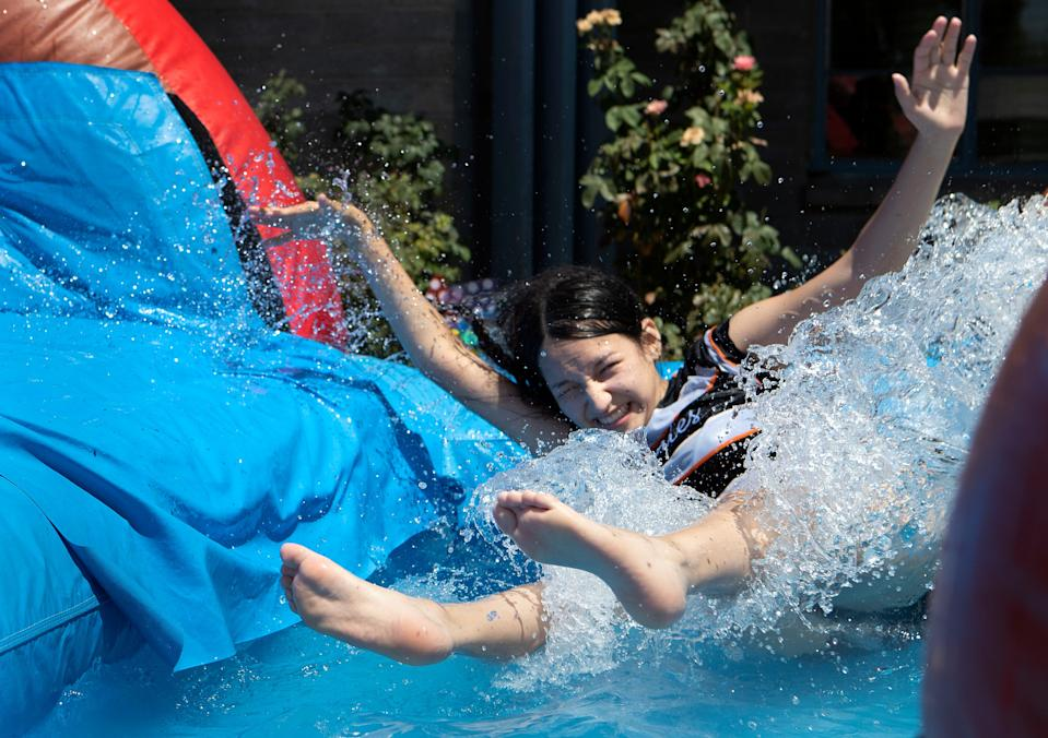 Noemi Amador, 15, cools off in a water feature in the front yard of her home in Thermal, Calif., on Friday, July 31, 2020. An excessive heat warning has been issued for the Coachella Valley.