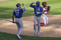 Kansas City Royals' Whit Merrifield, center, celebrates with Hunter Dozier, left, after hitting a solo home run as Chicago White Sox catcher James McCann looks to the field during the eighth inning of a baseball game in Chicago, Sunday, Aug. 30, 2020. (AP Photo/Nam Y. Huh)