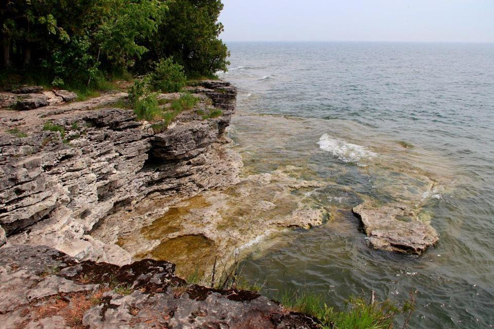 <p>An idyllic peninsula resting between Green Bay and Lake Michigan, Door County, Wisconsin cuts jagged cliffs and rocky coastline into the Green Bay harbor. Door County is dotted with lush evergreens and in the summer, makes the perfect swimming hole destination for locals and tourists alike.</p>