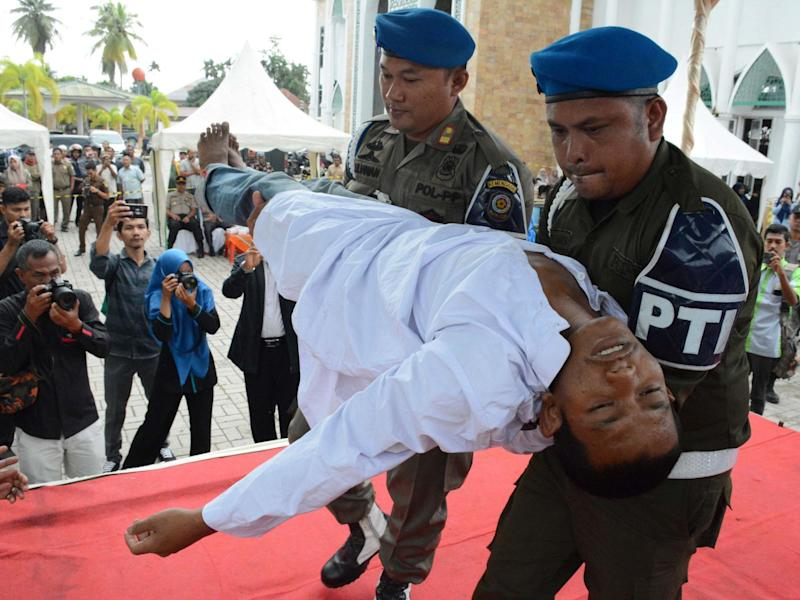 An Indonesian man faints after he was whipped in public on charges of engaging in sexual relations, in Aceh Timur: AFP via Getty Images